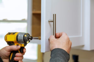 person replacing cabinet pull with drill